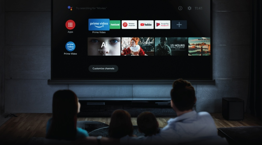 a family in the living room watching on a projector with Android TV
