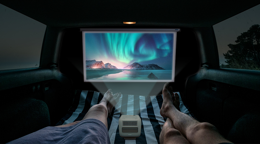 two people watching movies on a portable projector inside of a camper RV or campervan