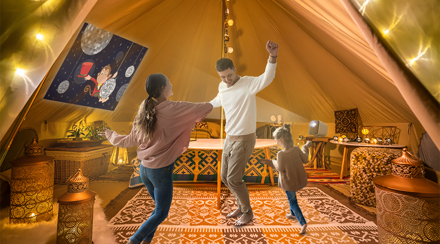 a family of three dancing to a children's movie on a portable projector when glamping