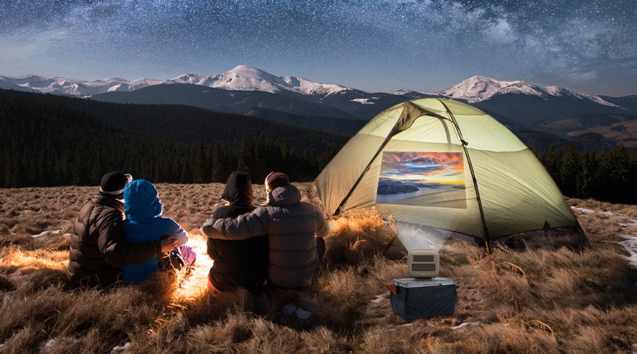 4 friends camping in the wild and watching movies under the stars with an outdoor projector