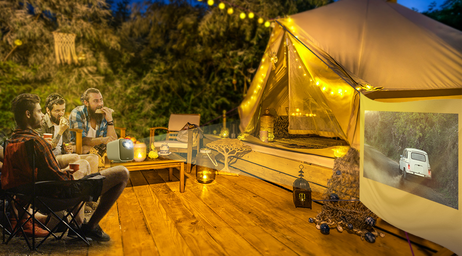 three friends get together at a glamping site watching movies on a portable projector