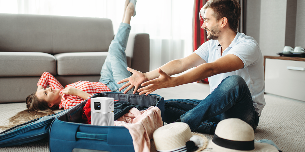 a couple packing luggage for travel and include a portable projector for a leisure trip