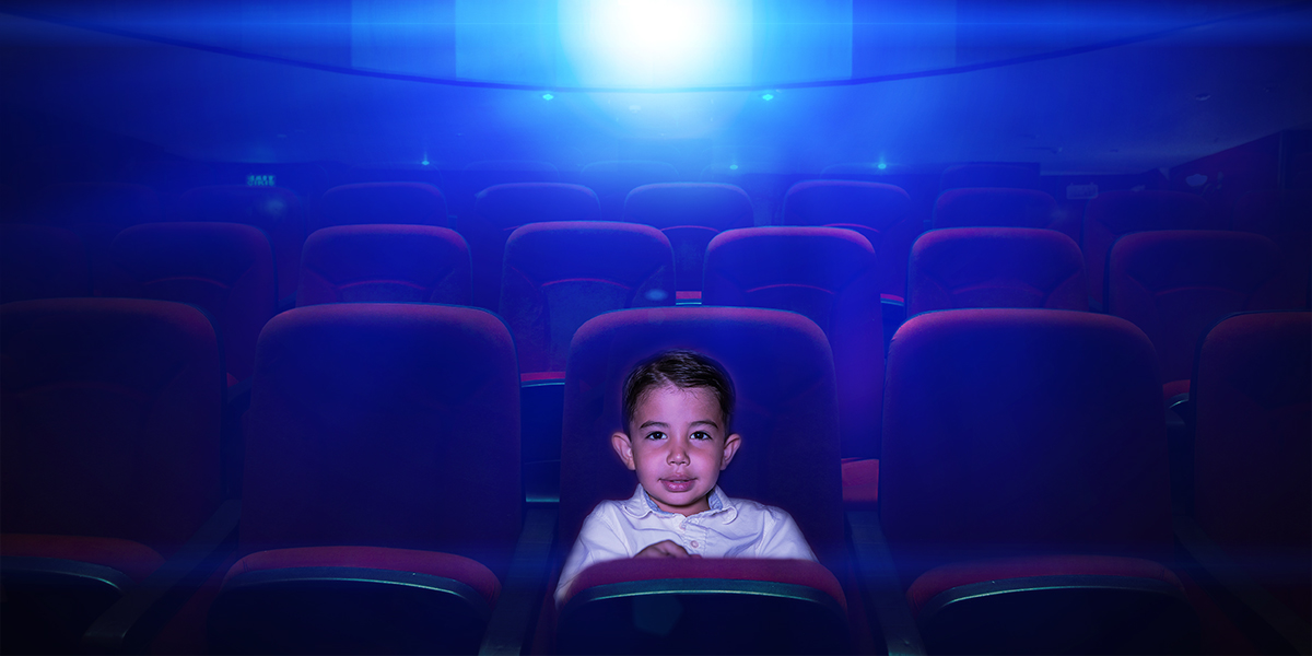 a kid is sitting in the cinema watching movies in the style of cinema paradiso