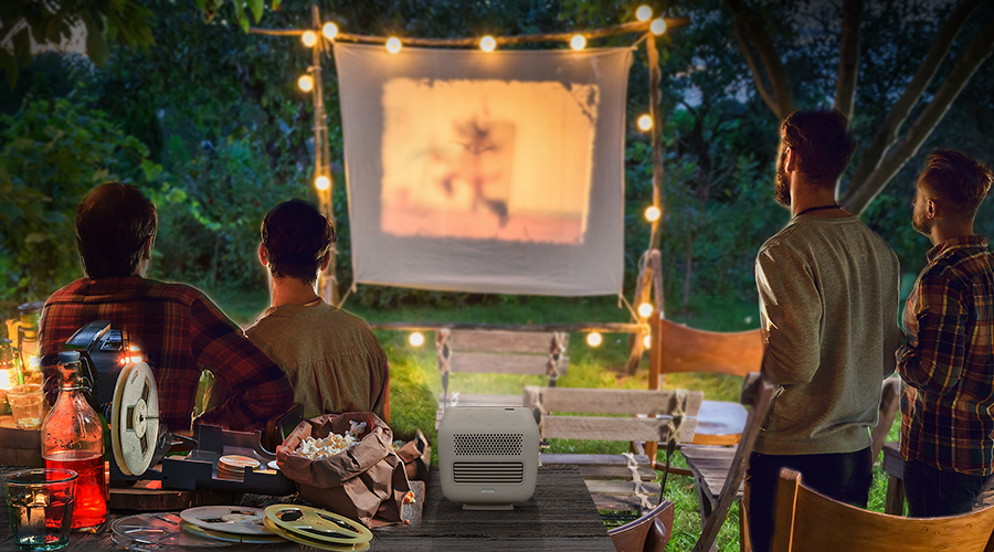 4 friends gather in the backyard and enjoy outdoor cinema with a portable projector
