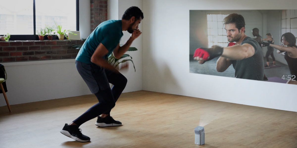 a guy is doing boxing exercise at home to a portable projector