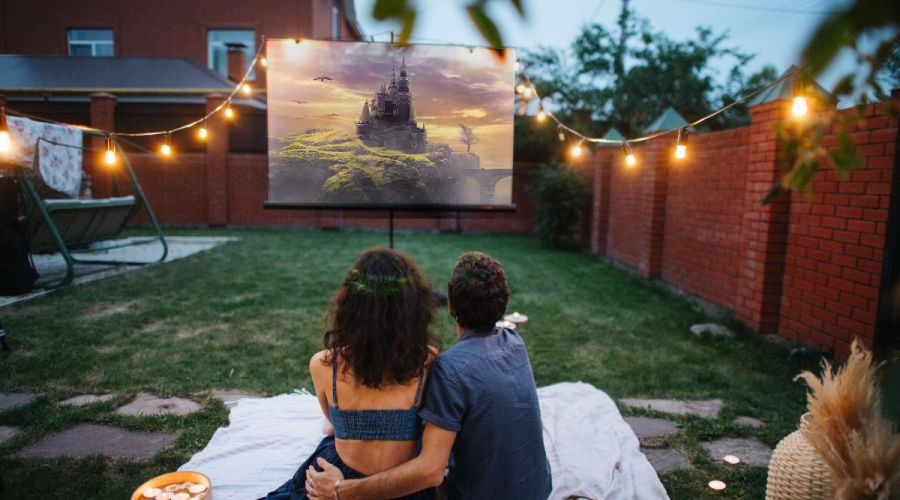 A couple preparing to watch movies on a projector in the backyard