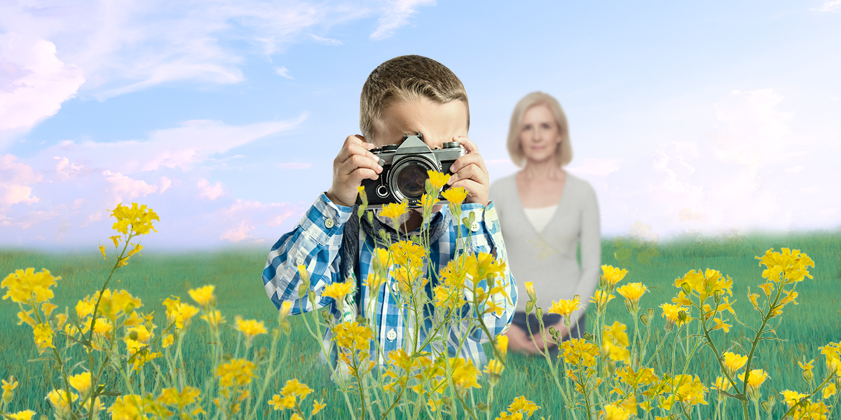 a boy taking photos of the rape flower while an older woman standing behind him and smiling