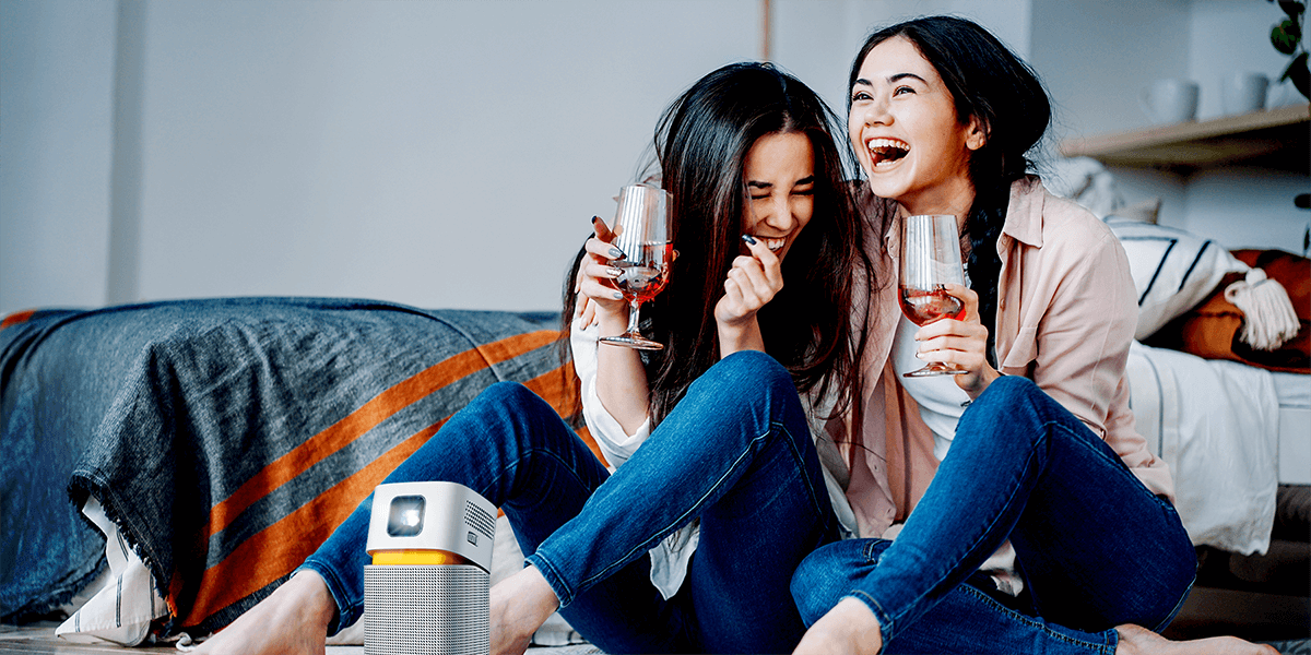 two girls enjoying big screen entertainment on a mini portable projector in a small room