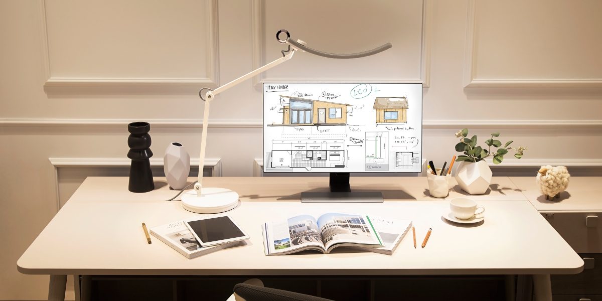 LED desk lamp lights up a big table with tablet and coffee